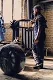 Bearded mechanic with unpacked car`s tire. Bearded mechanic with unpacked car`s tire near the tire changer machine in a workshop Stock Photography