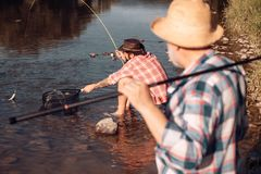 Bearded men catching fish. lear water river. Hobby sport activity. Elegant bearded man and brutal hipster fishing. Guy