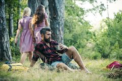 Bearded man drinking coffee or tea by campfire. Two girls in retro dresses walking on path in woods, turn back. Bearded men drinking coffee or tea by campfire stock photo