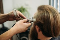 Bearded man having a haircut with a hair clippers. Closeup view with shallow depth of field stock photos