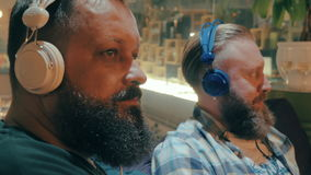 Bearded men in headphones enjoying music. Two bearded men relaxing on the sofa in trade centre and listening to music in headphones stock footage