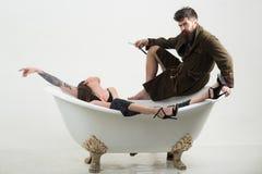 Bearded man hold shaving razor. Man with bearded face enjoy bath with sensual woman. Bearded man with unshaven face. Bearded men hold shaving razor. Man with royalty free stock image