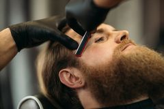 Bearded man with long beard getting stylish hair shaving , haircut , with razor by barber in barbershop stock photo