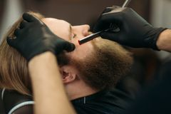 Bearded man with long beard getting stylish hair shaving , haircut , with razor by barber in barbershop stock photography