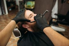 Bearded man with long beard getting stylish hair shaving , haircut , with razor by barber in barbershop royalty free stock photo