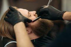 Bearded man with long beard getting stylish hair shaving , haircut , with razor by barber in barbershop. Bearded men with long beard getting stylish hair shaving stock images