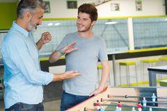 Bearded man playing table soccer with young worker Royalty Free Stock Image
