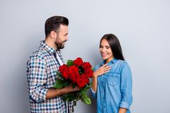 Bearded man presenting bouquet of red roses to his charming girl. Bearded men presenting bouquet of red roses to his charming girlfriend over grey background Royalty Free Stock Photos