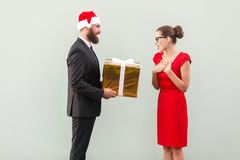 Bearded man in red cup give a present beautiful woman. Bearded men in red cup give a present beautiful woman. Studio shot on gray background Royalty Free Stock Photo