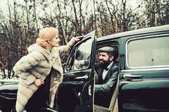 Bearded man and sexy woman in fur coat. Couple in love on romantic date. Travel and business trip or hitch hiking. Retro stock images