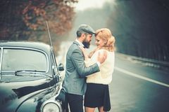 Bearded man and sexy woman in fur coat. Travel and business trip or hitch hiking. Retro collection car and auto repair stock photos