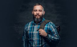 Middle age male holds backpack on a shoulder. A bearded middle age male dressed in a plaid shirt holds backpack on a shoulder Stock Photos