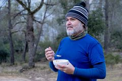 Man dressed in mountain clothes and a woolen hat breakfast a bowl of cereal in the woods stock images