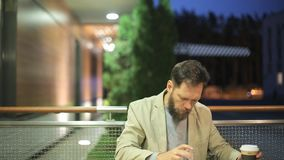 A bearded middle-aged man of Caucasian appearance is sitting at a table in a summer cafe in the evening, watching the. News on the screen of a tablet , drinking stock footage