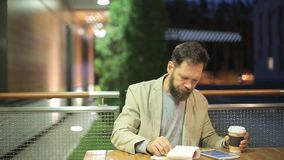 A bearded middle-aged man of Caucasian appearance is sitting at a table in a summer cafe in the evening, watching the. News on the screen of a tablet , drinking stock video footage