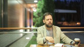 A bearded middle-aged man of Caucasian appearance is sitting at a table in a summer cafe in the evening, watching the. News on the screen of a tablet , drinking stock video
