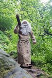 The bearded monk carries log. Stock Image