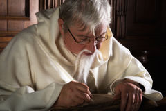 Bearded monk writing with quill Stock Images