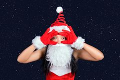 Bearded Mrs. Claus looks to the camera. With her hands imitating the telescope, background of stars stock photos