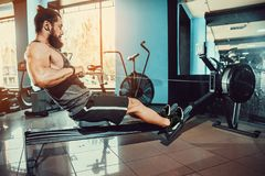 Muscular fit man using rowing machine at gym. Bearded Muscular Fit Man Ssing Rowing Machine at Functional Training Gym Royalty Free Stock Images