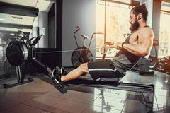 Muscular fit man using rowing machine at gym. Bearded Muscular Fit Man Ssing Rowing Machine at Functional Training Gym Stock Photos
