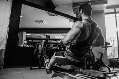 Muscular fit man using rowing machine at gym. Bearded Muscular Fit Man Using Rowing Machine at Functional Training Gym Stock Photos