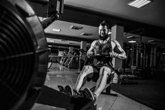 Muscular fit man using rowing machine at gym. Bearded Muscular Fit Man Using Rowing Machine at Functional Training Gym Royalty Free Stock Image