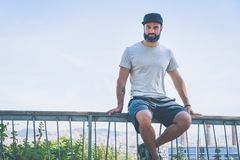Bearded muscular hipster man model wearing gray blank t-shirt and a black baseball cap with space for your logo or. Design in casual urban style.Green palm and Royalty Free Stock Photos