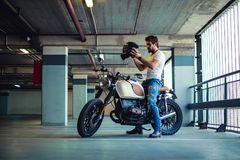 Man putting on motorcycle helmet in a garage stock image