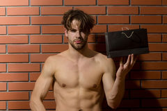 Bearded muscular man with sexy body holds shopping bag, package Royalty Free Stock Photography