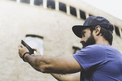 Bearded muscular man wearing black snapback cap and making selfie with his own smartphone. Man walking on street and royalty free stock images