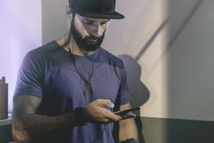 Bearded muscular man wearing black snapback cap standing on cafe with headphones. Men using mobile phone for listening. Digital music on smartphone.Blurred Stock Image