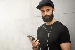 Bearded Muscular Man Wearing Black Tshirt Blank Snapback Cap Summer Time.Young Men Smiling Opposite Empty Gray Concrete royalty free stock images