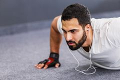 Man Does Push Ups. Bearded muscular man wears white t-shirt with headphones does floor push up workout in the gym Stock Images