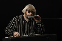 Bearded musician closing his eyes while singing. Bearded grey haired musician closing his eyes while singing on black background Royalty Free Stock Photos