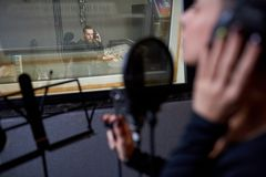 Operator working with singer in studio. Bearded operator with headset sitting at console and watching young women singing in recording studio Royalty Free Stock Photos