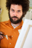 Bearded painter in his studio. Close-up of a painter in his studio, ready to paint an image Royalty Free Stock Photos