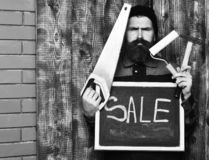 Bearded painter holding various building tools and board, serious face. Bearded painter man, long beard, brutal caucasian hipster with moustache holding various stock photography