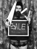 Bearded painter holding various building tools and board, serious face. Bearded painter man, long beard, brutal caucasian hipster with moustache holding various royalty free stock images