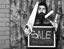 Bearded painter holding various building tools and board, surprised face. Bearded painter man, long beard, brutal caucasian hipster with moustache holding royalty free stock photos