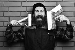Bearded painter man holding various building tools with happy face. Bearded painter man, long beard, brutal caucasian hipster with moustache in uniform holding stock images