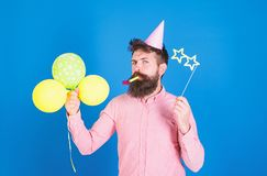 Bearded party entertainer at kids celebration, International children day concept. Man with bright balloons, paper. Glasses and cap at birthday party. Bearded royalty free stock images
