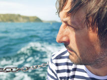 Bearded pensive male looking at the sea from yacht. Thoughtful successful adult sailor on bright sunny summer day enjoying vacation holidays Stock Photos