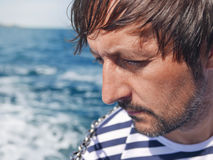 Bearded pensive male looking at the sea from yacht. Thoughtful successful adult sailor on bright sunny summer day enjoying vacation holidays Royalty Free Stock Photos