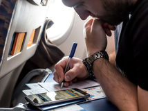 Bearded pensive Man filling Immigration Form in Aircraft. Using mobile Phone to check Travel Details and Data stock photo