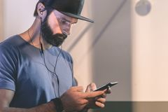 Bearded pensive man wearing black snapback cap standing on cafe with headphones. Men using mobile phone for listening. Digital music on smartphone.Blurred Stock Photography