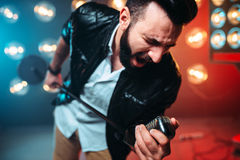 Bearded performer with microphone sing a song. Brutal bearded performer with microphone sing a song on the stage with the decorations of lights Royalty Free Stock Images