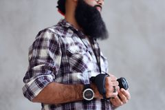 Bearded photographer holds compact DSLR camera over grey background. stock photo