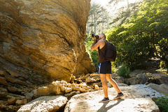 Bearded photographer man trekking among forest and mountains and taking pictures with dslr camera. Horizontal shape Royalty Free Stock Photography