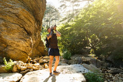 Bearded photographer man trekking among forest and mountains and taking pictures with dslr camera. Horizontal shape Stock Images